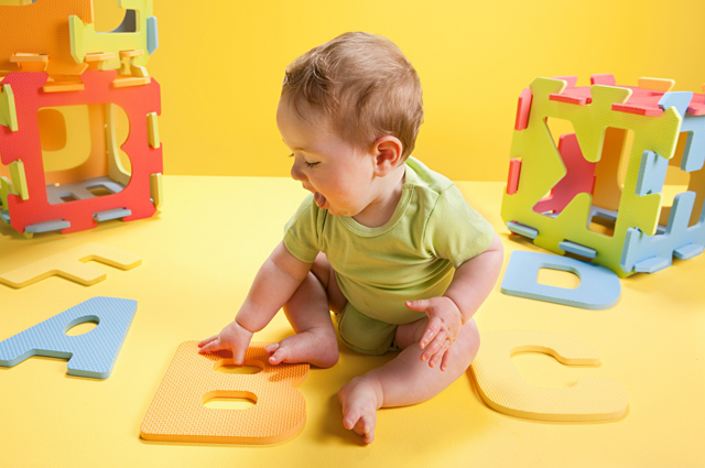 Baby boy playing with toy alphabet letters